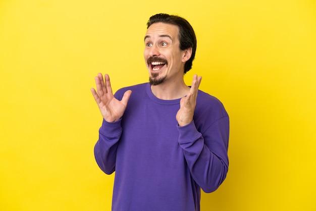 Jonge blanke man geïsoleerd op gele achtergrond met verrassing gezichtsuitdrukking