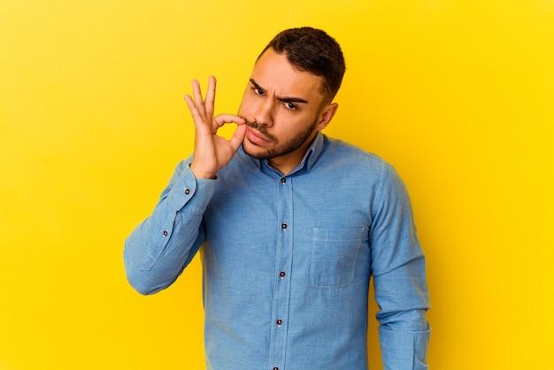 Jonge blanke man geïsoleerd op gele achtergrond met vingers op lippen die een geheim houden.