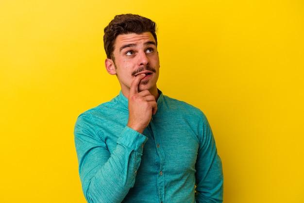 Jonge blanke man geïsoleerd op gele achtergrond ontspannen denken over iets kijken naar een kopie ruimte.