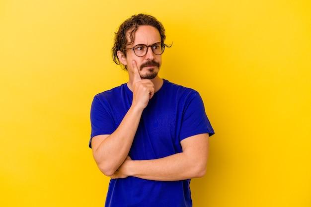 Jonge blanke man geïsoleerd op gele achtergrond overweegt, een strategie plannen, na te denken over de manier van een bedrijf.