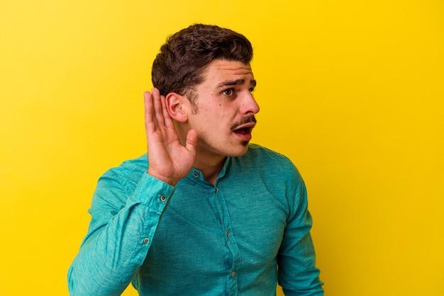 Jonge blanke man geïsoleerd op gele achtergrond probeert te luisteren naar een roddel.