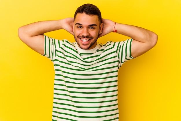 Jonge blanke man geïsoleerd op gele achtergrond strekkende armen, ontspannen positie.