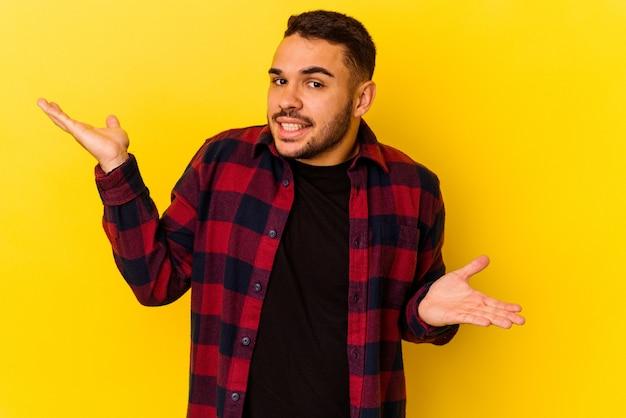Jonge blanke man geïsoleerd op gele achtergrond verward en twijfelachtig schouders ophalen om een kopie ruimte te houden.