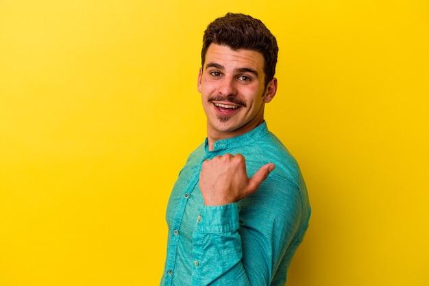 Jonge blanke man geïsoleerd op gele achtergrond wijst met duimvinger weg, lachend en zorgeloos.