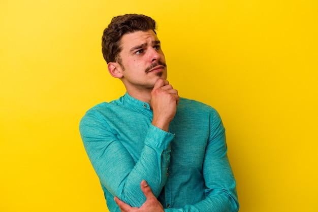 Jonge blanke man geïsoleerd op gele achtergrond zijwaarts kijkend met twijfelachtige en sceptische uitdrukking.