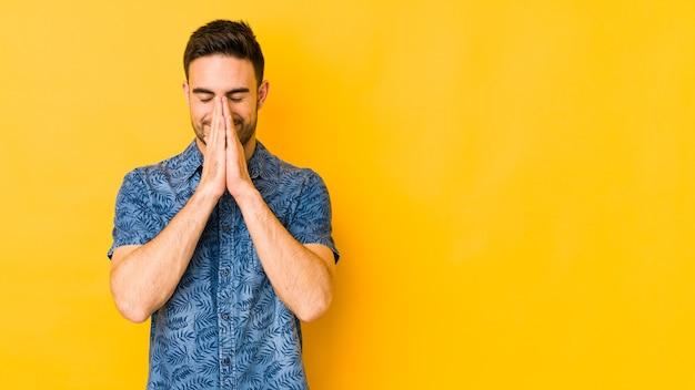Jonge blanke man geïsoleerd op gele bakground hand in hand bidden in de buurt van de mond, voelt zich zelfverzekerd.
