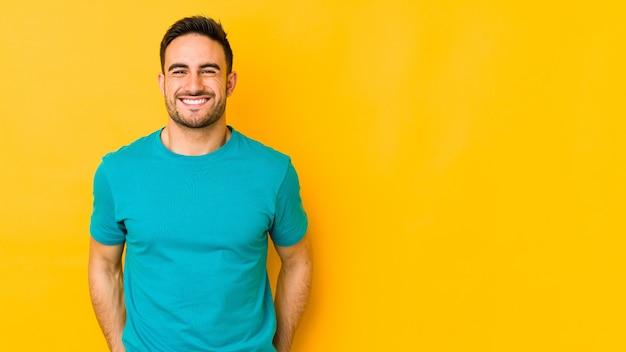 Jonge blanke man geïsoleerd op gele bakground lacht en sluit de ogen, voelt zich ontspannen en gelukkig.