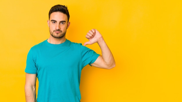 Jonge blanke man geïsoleerd op gele bakground met een afkeer gebaar, duimen naar beneden. meningsverschil concept.