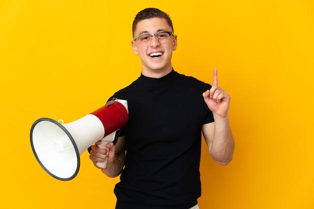 Jonge blanke man geïsoleerd op gele muur met een megafoon en wijst op een geweldig idee