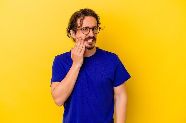 Jonge blanke man geïsoleerd op gele muur met een sterke tandenpijn, kiespijn