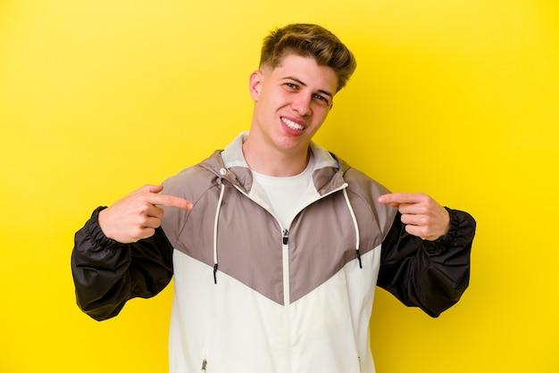 Jonge blanke man geïsoleerd op gele muur wijst naar beneden met vingers, positief gevoel