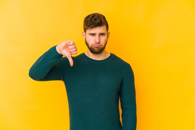 Jonge blanke man geïsoleerd op gele ruimte met een afkeer gebaar, duimen naar beneden. meningsverschil concept.