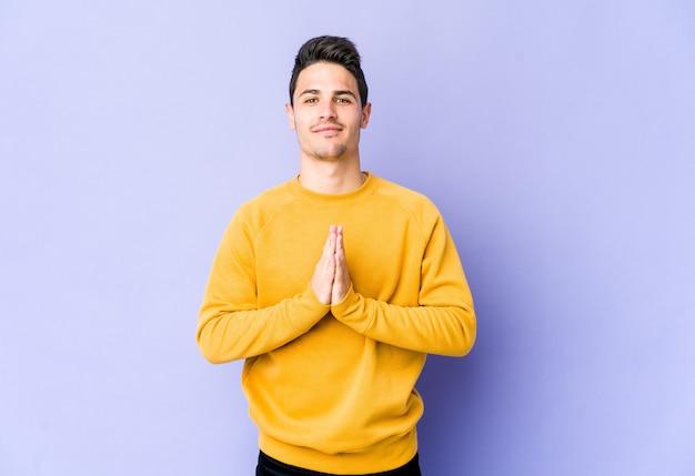 Jonge blanke man geïsoleerd op paarse achtergrond bidden, toewijding, religieuze persoon op zoek naar goddelijke inspiratie.