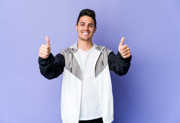 Jonge blanke man geïsoleerd op paarse achtergrond glimlachend en duim opheffen