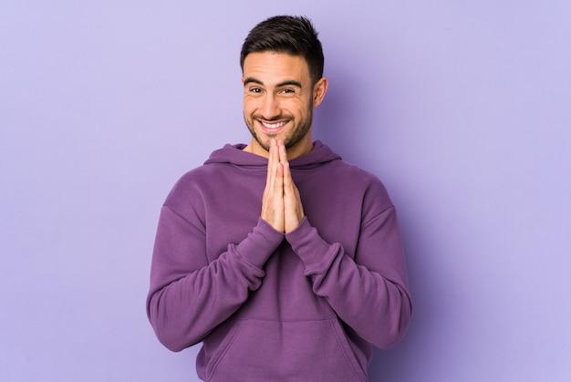Jonge blanke man geïsoleerd op paarse achtergrond hand in hand bidden in de buurt van mond, voelt vertrouwen.