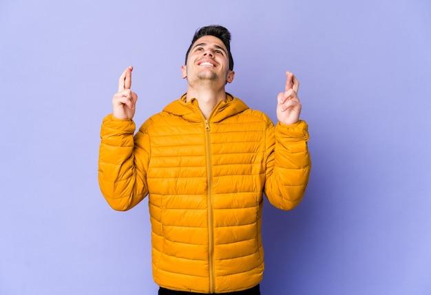 Jonge blanke man geïsoleerd op paarse muur kruising vingers voor geluk