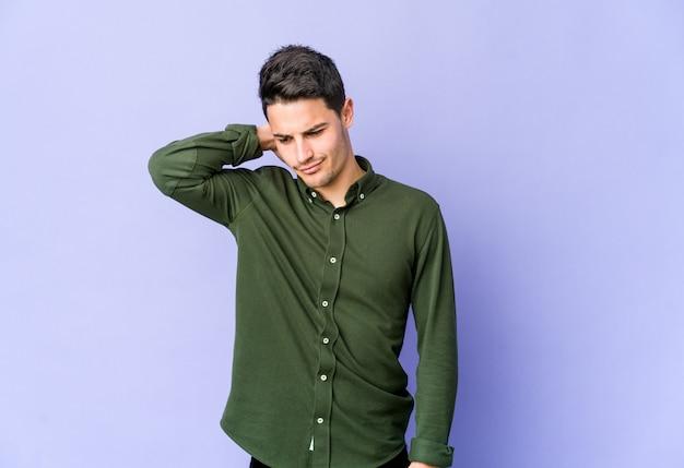 Jonge blanke man geïsoleerd op paarse muur nekpijn lijden als gevolg van een zittende levensstijl.