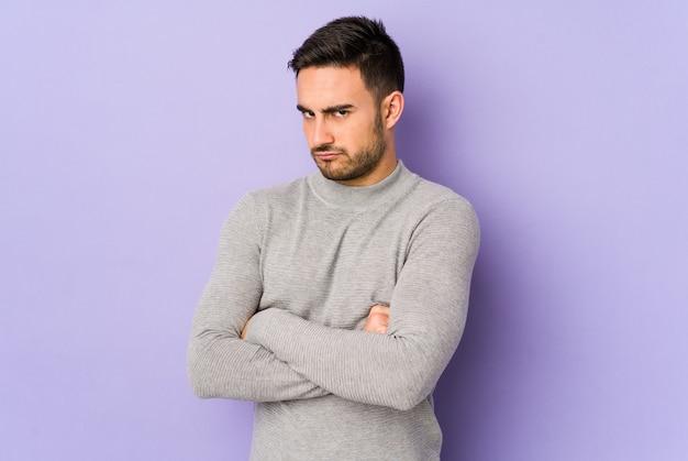 Jonge blanke man geïsoleerd op paarse ruimte fronsend gezicht in ongenoegen, houdt armen gevouwen.