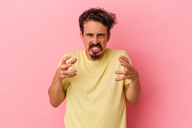 Jonge blanke man geïsoleerd op roze achtergrond boos schreeuwen met gespannen handen.