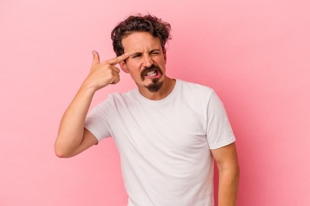 Jonge blanke man geïsoleerd op roze achtergrond die betrekking hebben op oren met handen.