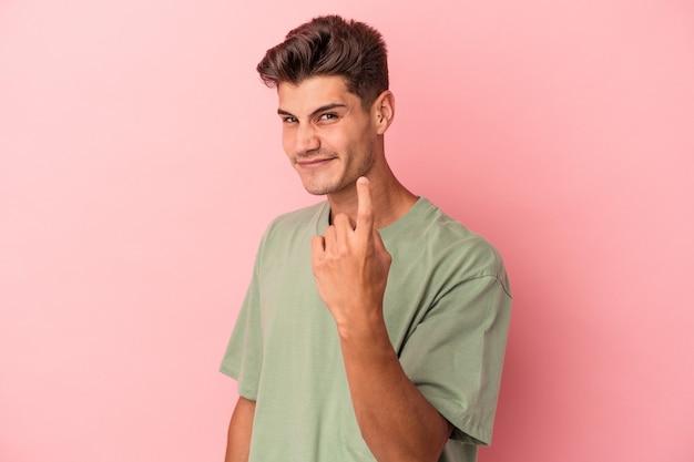Jonge blanke man geïsoleerd op roze achtergrond die met de vinger naar je wijst alsof uitnodigend dichterbij komt.