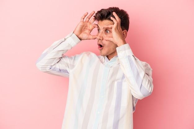 Jonge blanke man geïsoleerd op roze achtergrond die ogen open houdt om een succeskans te vinden.