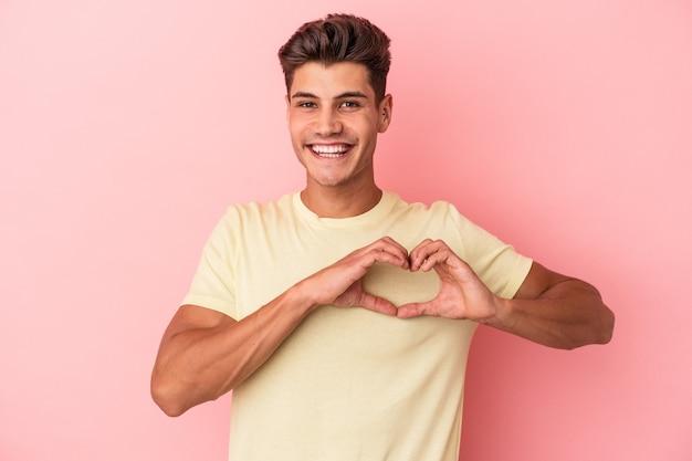 Jonge blanke man geïsoleerd op roze achtergrond glimlachend en met een hartvorm met handen.
