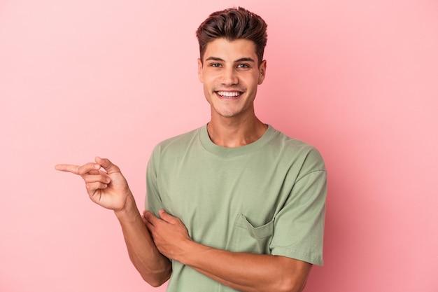 Jonge blanke man geïsoleerd op roze achtergrond glimlachend vrolijk wijzend met wijsvinger weg.