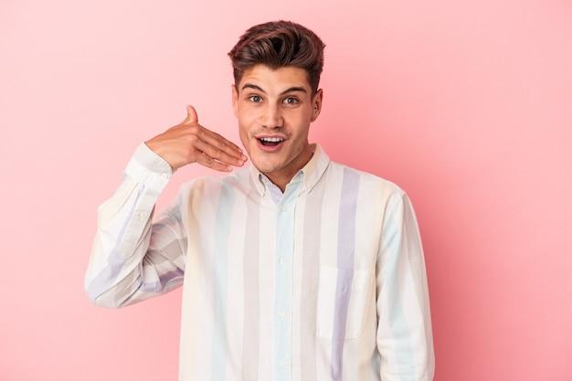 Jonge blanke man geïsoleerd op roze achtergrond lachen om iets, mond bedekken met handen.