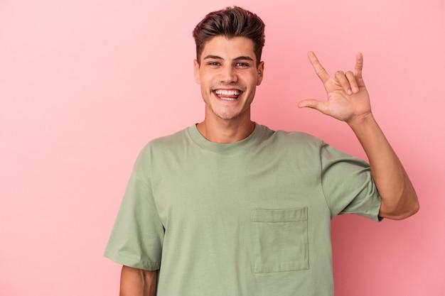 Jonge blanke man geïsoleerd op roze achtergrond met een gebaar van hoorns als een concept van de revolutie.
