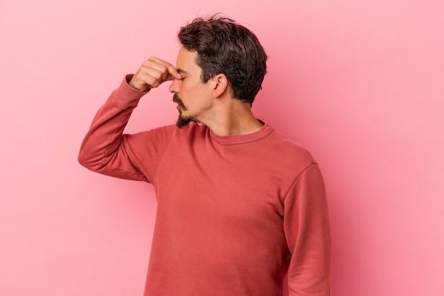 Jonge blanke man geïsoleerd op roze achtergrond met hoofdpijn, aanraken van de voorkant van het gezicht.