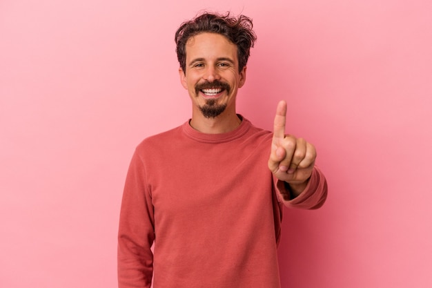 Jonge blanke man geïsoleerd op roze achtergrond met nummer één met vinger.