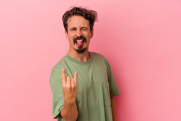 Jonge blanke man geïsoleerd op roze achtergrond met rock gebaar met vingers