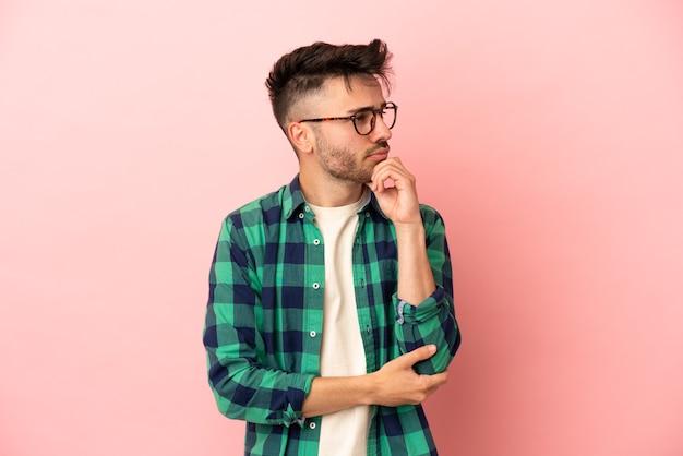 Jonge blanke man geïsoleerd op roze achtergrond met twijfels en denken