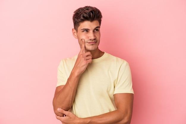 Jonge blanke man geïsoleerd op roze achtergrond overweegt, een strategie plannen, nadenken over de manier van een bedrijf.