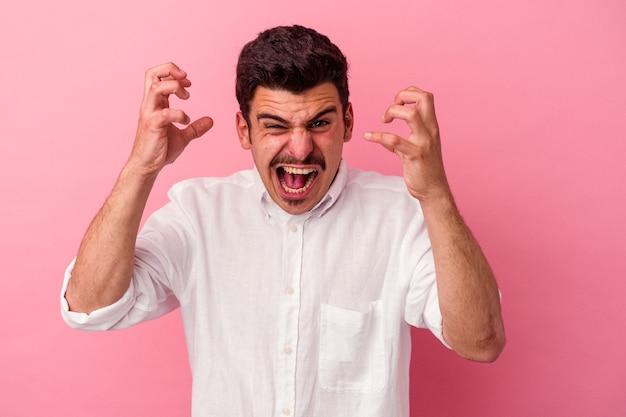 Jonge blanke man geïsoleerd op roze achtergrond schreeuwen van woede.