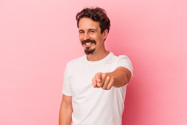 Jonge blanke man geïsoleerd op roze achtergrond vrolijke glimlach wijzend naar voren.