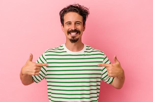 Jonge blanke man geïsoleerd op roze achtergrond wijst naar beneden met vingers, positief gevoel.