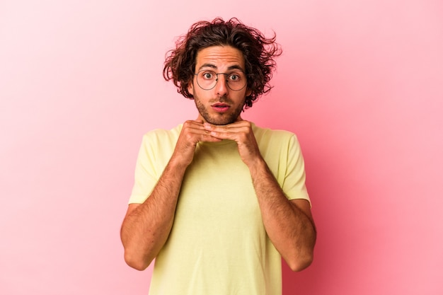 Jonge blanke man geïsoleerd op roze bakcground bidden voor geluk, verbaasd en openende mond op zoek naar voren.