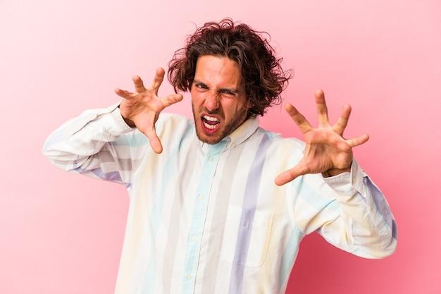 Jonge blanke man geïsoleerd op roze bakcground boos schreeuwen met gespannen handen.