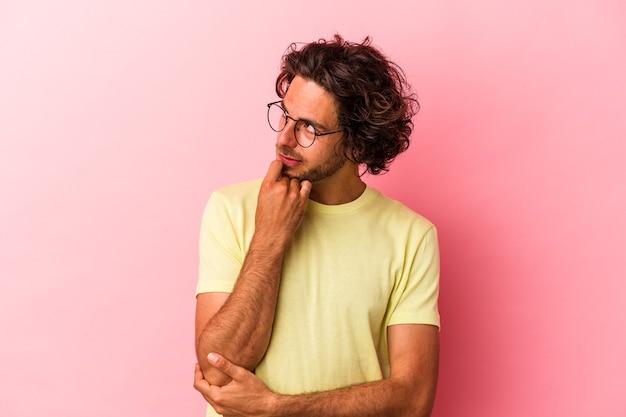 Jonge blanke man geïsoleerd op roze bakcground denken en opzoeken, reflecterend zijn, nadenken, een fantasie hebben.