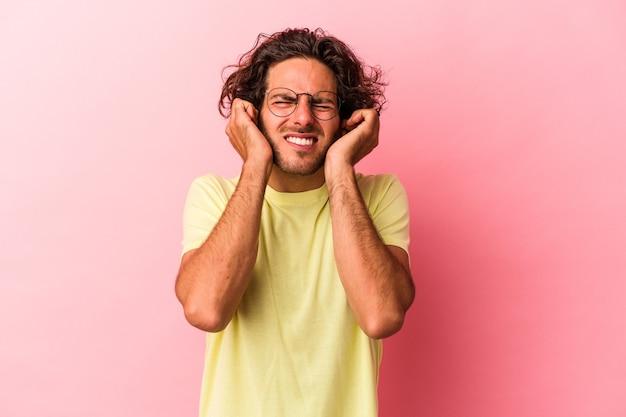 Jonge blanke man geïsoleerd op roze bakcground die oren bedekt met handen.