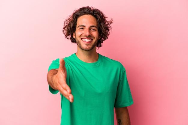 Jonge blanke man geïsoleerd op roze bakcground glimlachend en duim omhoog