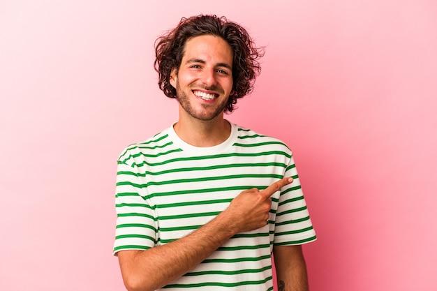 Jonge blanke man geïsoleerd op roze bakcground glimlachend en opzij wijzend, met iets op lege ruimte.