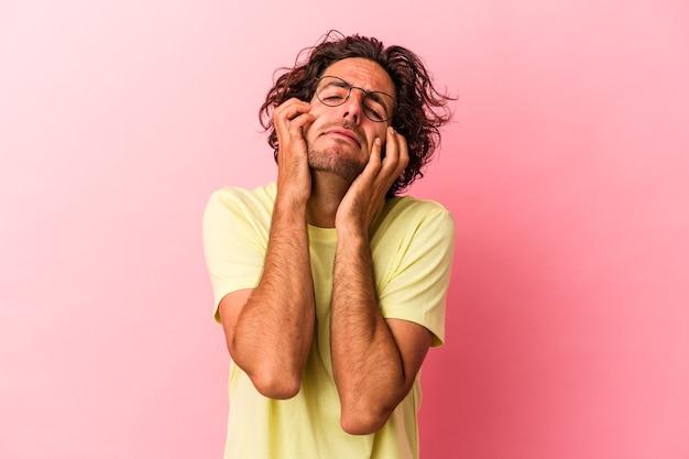 Jonge blanke man geïsoleerd op roze bakcground huilen, ongelukkig met iets, pijn en verwarring concept.