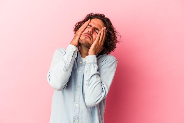 Jonge blanke man geïsoleerd op roze bakcground jammerend en huilend troosteloos.