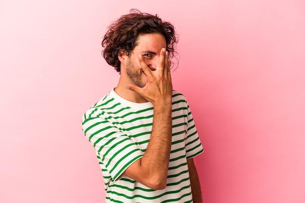Jonge blanke man geïsoleerd op roze bakcground knipperen naar de camera door vingers, beschaamd bedekkend gezicht.