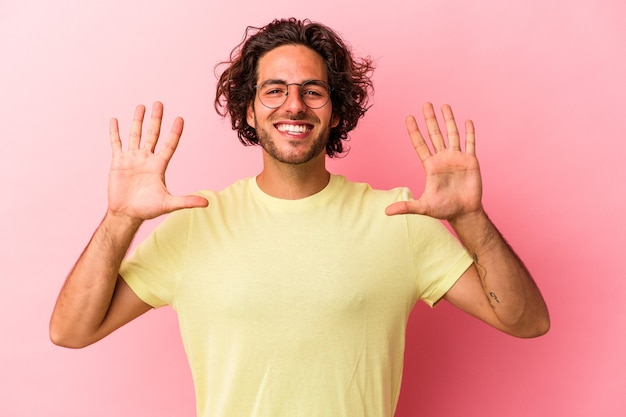 Jonge blanke man geïsoleerd op roze bakcground met nummer tien met handen.