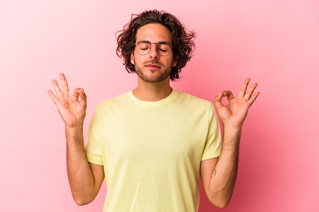 Jonge blanke man geïsoleerd op roze bakcground ontspant na een zware werkdag, ze voert yoga uit.