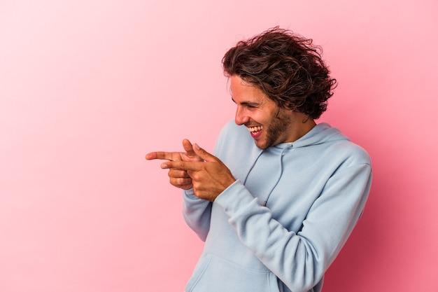 Jonge blanke man geïsoleerd op roze bakcground punten met duimvinger weg, lachend en zorgeloos.